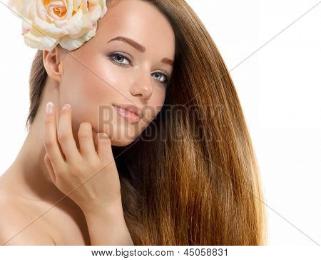 Beauty Girl. Beautiful Model with Rose Flower Touching her Face. Healthy Long Hair and Perfect Clear Skin. Youth. Isolated on White Background. Blowing Hair. Skincare concept