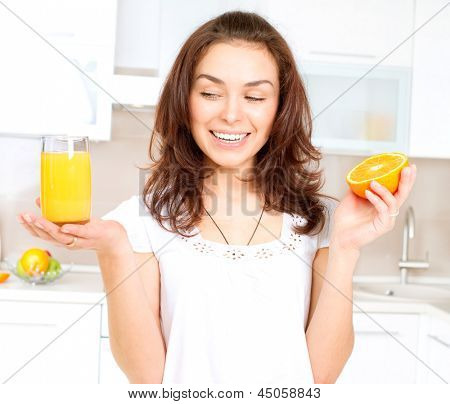 Young and Healthy Woman with Orange Juice in the Kitchen. Diet and Healthy Eating Concept. Natural Fresh Orange Juice