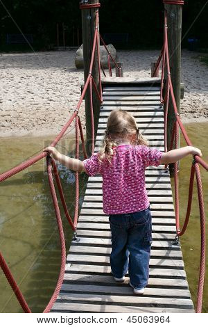 Little Girl Walking On A Suspended Wooden Bridge