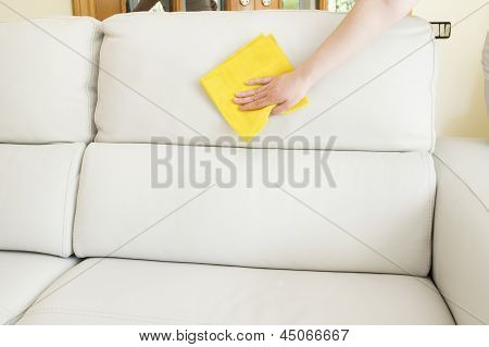 cleaning a beige sofa with a cloth