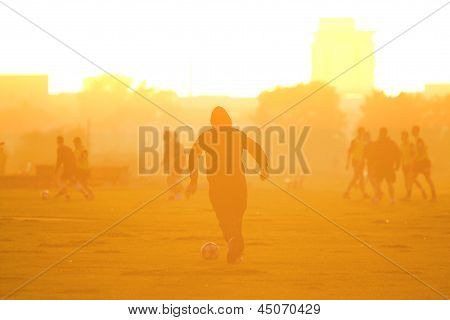 Footballer runs with soccer ball into sunset