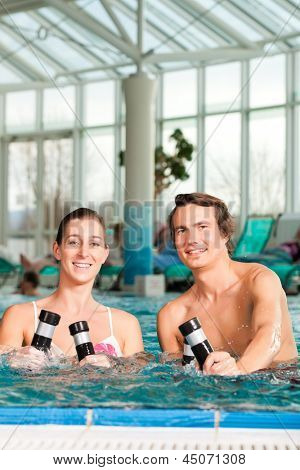 Fitness - a young couple - man and woman - doing sports and gymnastics or water aerobics under water in swimming pool or spa with dumbbells