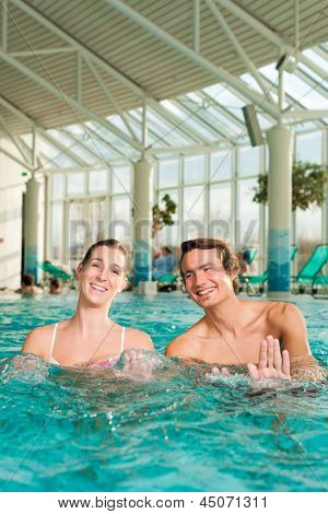 Fitness - a young couple - man and woman - doing sports and gymnastics or water aerobics under water in swimming pool or spa with current flow