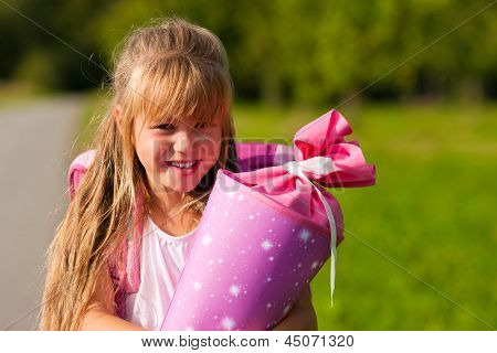 Proud kid having first day at school holding a traditional cone filled with sweet stuff