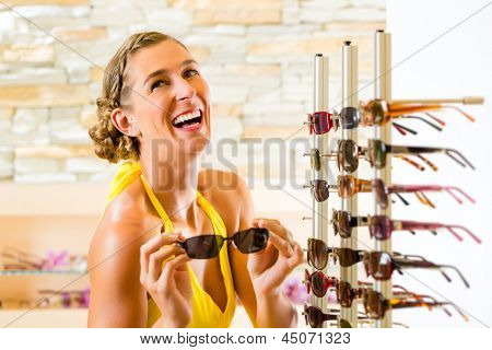 Young woman at optician with glasses, she is customer to the shop and buying some sunglasses