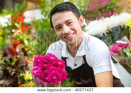 Friendly Asian florist or seller in a flower shop holding a flower bouquet