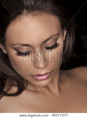 Close up portrait of beautiful young woman's face with fake lash extensions