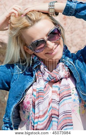 Beautiful blonde with jeans jacket, scarf, sunglasses and watch holding hair