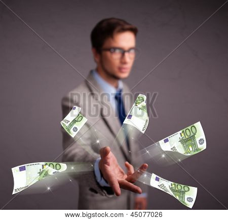 Handsome young man standing and throwing money