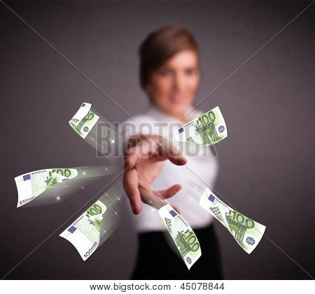 Pretty young woman standing and throwing money