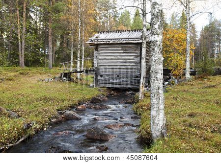 Brook menor e um edifício de madeira idoso.