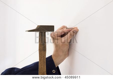 Closeup of a man hammering a nail into a wall white