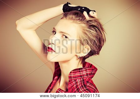 Portrait of a young fashionable model posing at studio with expression.