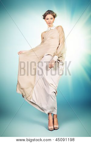 Charming fashionable model in elegant light dress posing at studio.