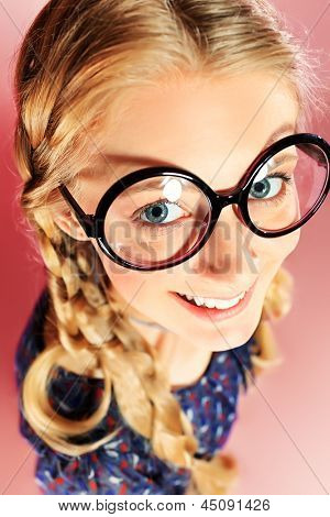 Portrait of a funny blonde girl in big round spectacles looking at camera. Retro style.
