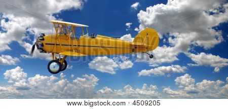 Vintage Biplane Over Clouds
