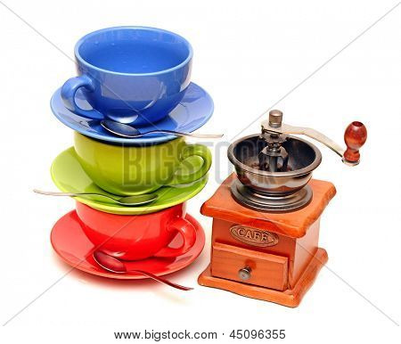 Colorful coffee mugs with coffee mill isolated on white