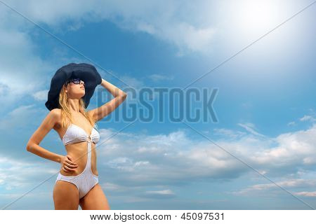 Woman in bikini wearing a hat by the sea