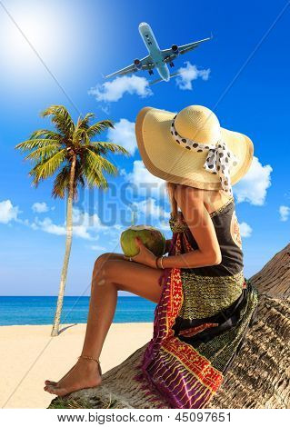 Woman in sarong on a coconut tree at the beach in a tropical resort