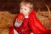 picture of riding-crop  - Little girl is sitting on pile of straw eating apple - JPG