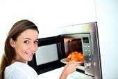 stock photo of oven  - Woman putting plate in microwave oven - JPG
