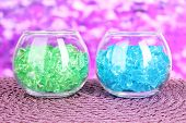 Glasses with colorful decorative stones on bright background