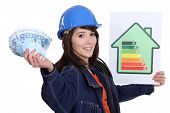 Tradeswoman holding up an energy efficiency rating chart and a wad of money
