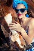 foto of redneck  - Beautiful young woman wearing blue dress with a horse outdoor - JPG