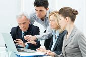 stock photo of teamwork  - Team Of Business People Working Together On A Laptop - JPG