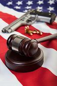 foto of bullet  - A wooden gavel on an american flag with a gun and bullets in the background - JPG