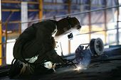 image of welding  - Worker in full protective gear and mask bending down using an industrial welding torch in a commercial building - JPG