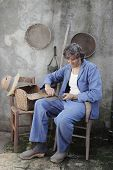 stock photo of machete  - man in a retro interior sharpening a machete - JPG