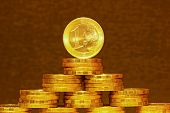 stock photo of copper coins  - One euro coin on top of a pyramid of coins - JPG