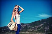 stock photo of country girl  - Beautiful young woman posing on a road over picturesque landscape - JPG