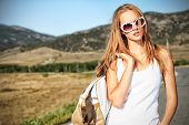 picture of independent woman  - Beautiful young woman posing on a road over picturesque landscape - JPG