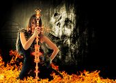 stock photo of pirate sword  - Warrior woman holding a fire sword with skull on background - JPG
