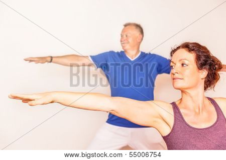 An image of a man and a woman doing yoga exercises