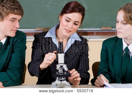 Teacher teaching microscope