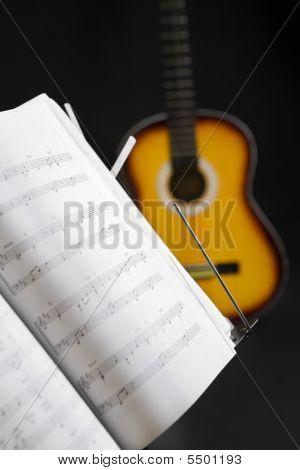 Acordes musicais e guitarra no fundo