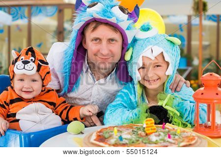 Father with daughter in monster costumes and baby boy in tiger costume celebrate the birthday in a cafe