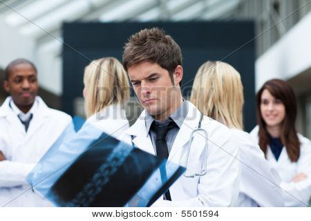 Serious Doctor Looking At An X-ray