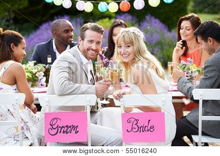 Bride And Groom Enjoying Meal At Wedding Reception
