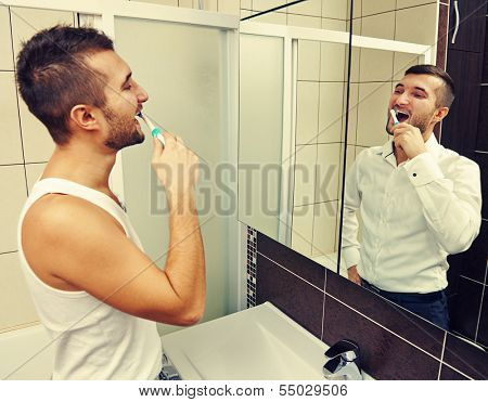 drowsy man brushing teeth and looking at successful businessman in the mirror