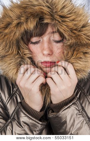 Young sad girl wearing winter coat warming herself with fur hood up