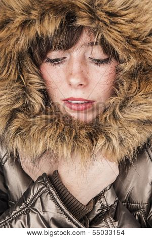 Young girl wearing winter coat warming herself with fur hood up