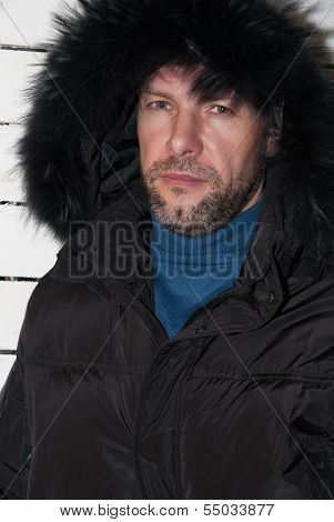 Portrait Of Confident Man Wearing Fur Hooded Parka Coat At The White Wall