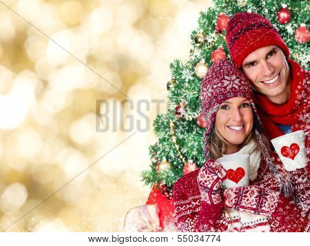 Happy couple drinking hot tea. Christmas background.