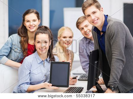 education, advertisement, techology and internet concept - group of smiling students with computer monitor and blank black tablet pc screen