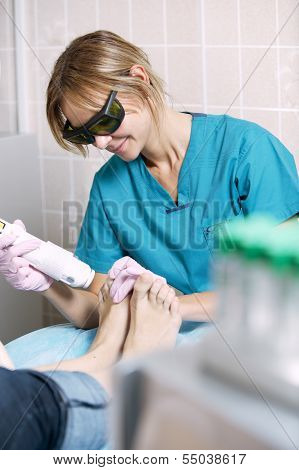 Podiatrist doing a foot laser treatment