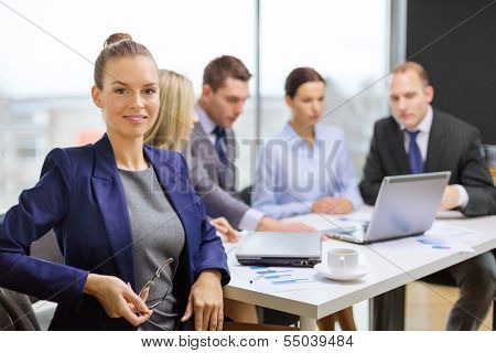 business, technology and office concept - smiling businesswoman with eyeglasses in office with team on the back